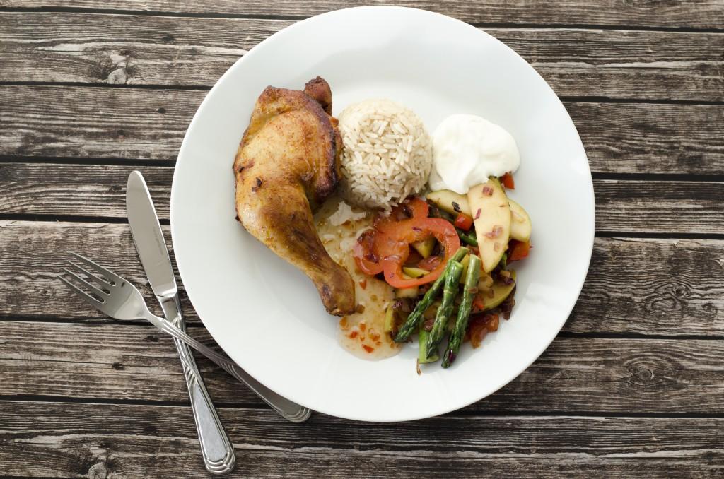 Grillet kylling med ris og salat på et fat